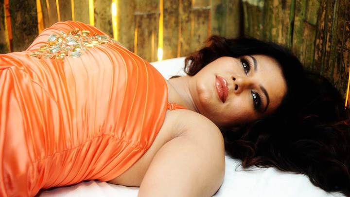 Rakhi Sawant Laying Pose In Orange Dress
